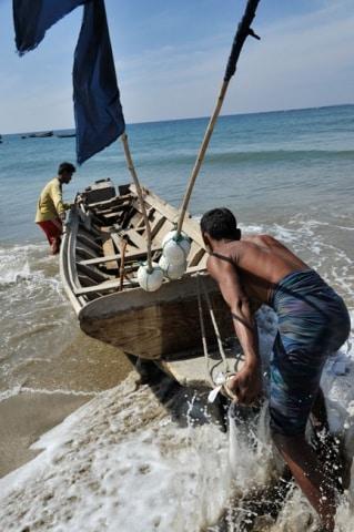 Deux pêcheurs mettent à l'eau leur barque dans le Golfe du Bengale Birmanie © Karmin Communication Photographie