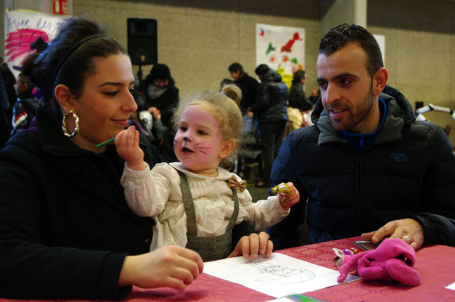Parents et leur petite fille avec les Pères Noël Verts du Secours Populaire français Isère lors du libre service de Noël à Echirolles