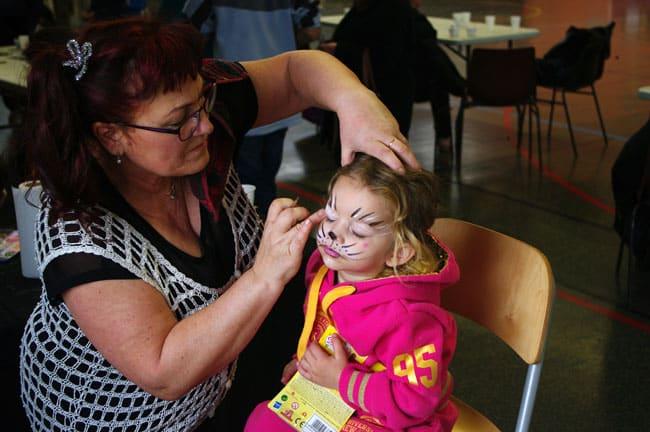 Maquillage d'un enfant par une bénévole avec les Pères Noël Verts du Secours Populaire français Isère lors du libre service de Noël à Echirolles