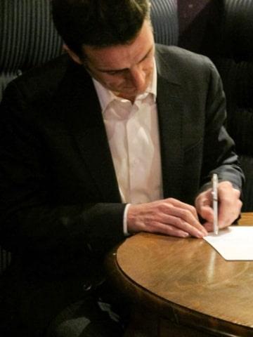 Eric Piolle de la liste Grenoble une ville pour tous signant la charte Anticor Isère contre la corruption des élus