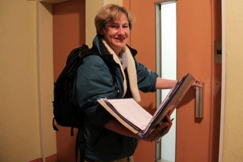 Jacqueline agent recenseur Insee à Grenoble dans un hall d'immeuble à la porte d'un ascenseur