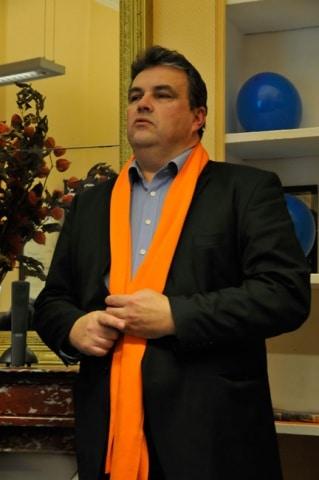 Philippe de Longevialle tête de liste de Imagine Grenoble présentant son programme dans son local de campagne le 25 février 2014 avec son écharpe orange