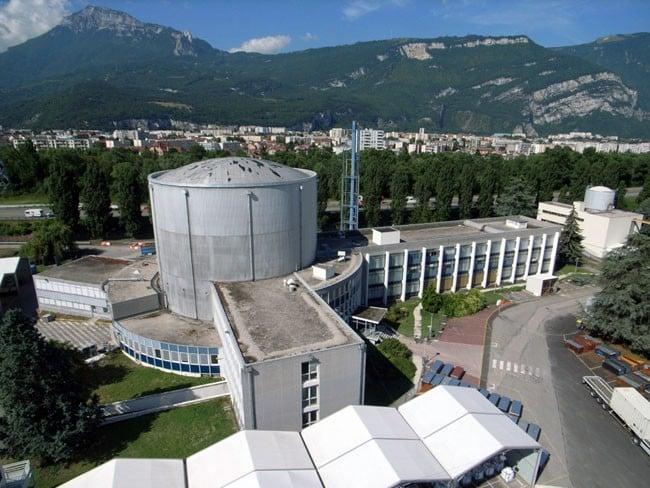 Vue aérienne du réacteur expérimental Siloé du CEA Grenoble et des tentes de l'aire de transit créée pour accueillir les déchets nucléaires issus du démantèlement irradié