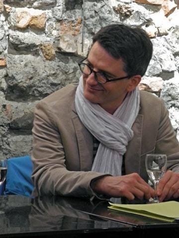 L'écrivain Nicolas Clément avec un verre à pied à la librairie La Dérive à Grenoble : photo de Yann Montigné