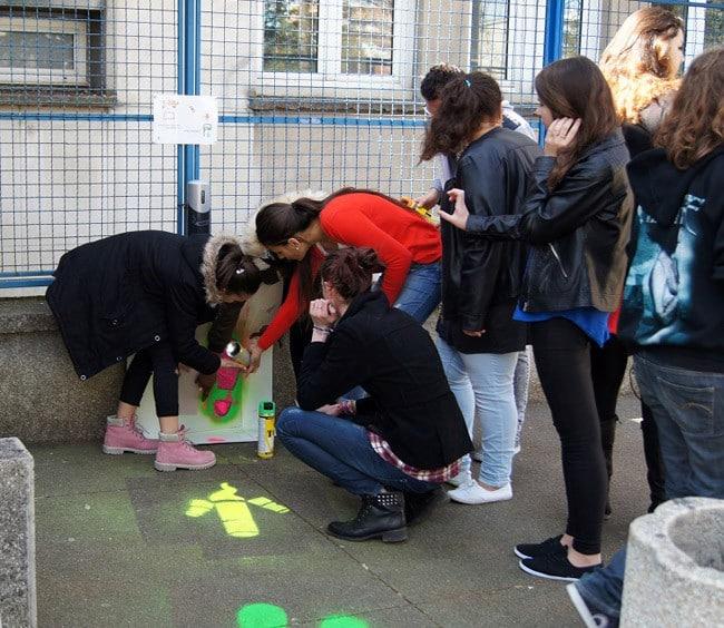 Élèves de seconde du lycée Mounier en train d'effectuer un marquage au sol incitatif vers les cendriers, à l'aide de pochoirs et de peintures fluos en vue du recyclage des mégots par Terracycle