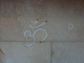 Inscription Om Shanti sur la poussière d'un mur - André Weill yoga en prison