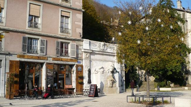 Place de la cymaise à Grenoble au début de la rue Saint Laurent avec vue sur L'Eco' Musée Le Mont Rachais un arbre et le lion © Delphine Chappaz - placegrenet.fr