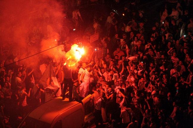 Supporter juché sur le toit d'une voiture avec un feu de bengale et de la fumée sur le cours Jean Jaurès à Grenoble à l'occasion de la qualification de l'Algérie pour les huitièmes de finale.