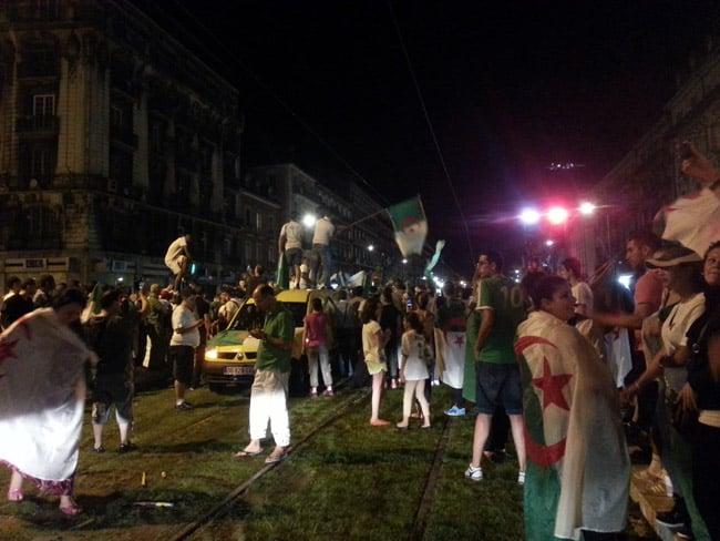 Supporters avec des drapeaux algériens sur la pelouse de la voie du tram E sur le cours Jean Jaurès à Grenoble à l'occasion de la qualification de l'Algérie pour les huitièmes de finale.