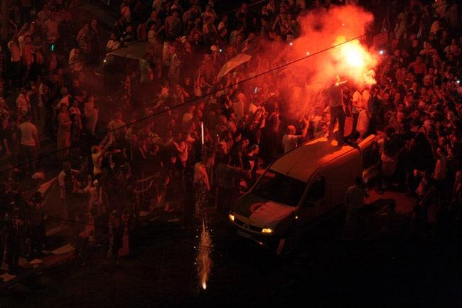 Supporter juché sur le toit d'une voiture avec un feu de bengale de la fumée et un tir de fusée sur la pelouse de la voie du tram E sur le cours Jean Jaurès à Grenoble à l'occasion de la qualification de l'Algérie pour les huitièmes de finale.