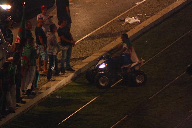 Supporter avec un drapeau algérien sur le dos pilotant un quad sur la pelouse du tram E sur le cours Jean Jaurès à Grenoble à l'occasion de la qualification de l'Algérie pour les huitièmes de finale.