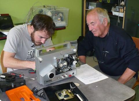 Un bénévole répare un vieux transistor en panne sous l'œil de son propriétaire. © Delphine Chappaz - placegrenet.fr