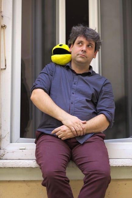 Florent Mathieu assis sur un rebord de fenêtre avec une peluche de Pacman sur l'épaule droite - blog Place Gre'net A la découverte du continent geek