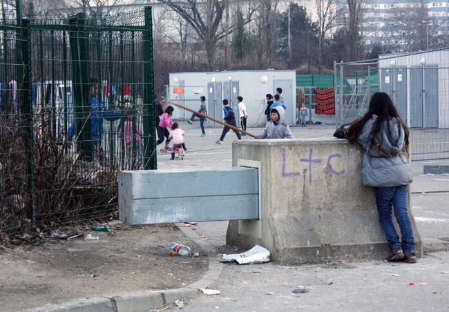 Des enfants jouent sur un parking devant le camps du CCAS à Grenoble qui héberge des Roms et des sans-abris.