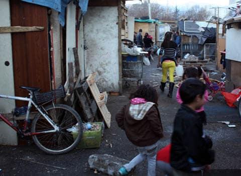 De jeunes enfants s'amusent dans le bidonville avenue Edmond Esmonin à Grenoble avec des cabanes en palettes de bois dans un camp abritant des Roms et des sans abris