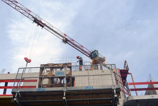 Une grue au dessus d'un bâtiment en construction avec un ouvrier à Grenoble. © Sidonie Hadoux