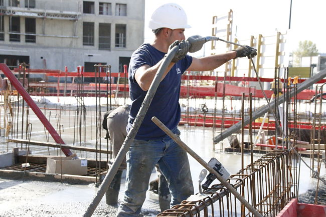 Un ouvrier du BTP soulève un câble par dessus des armatures métalliques sur un bâtiment en construction à Grenoble. © Fanny Chatchate