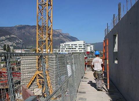 Un ouvrier du bâtiment et des travaux publics BTP porte une échelle sur un bâtiment en construction à Grenoble. © Fanny Chatchate