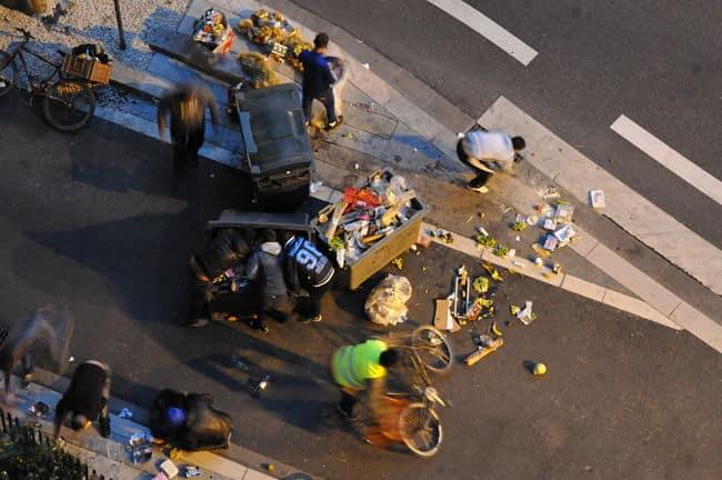 Des personnes fouillent dans la poubelle d'un supermarché à Grenoble. © Paul Turenne - placegrenet.fr