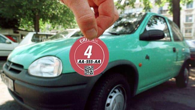 Une personne tient une nouvelle pastille Crit'air catégorie 4 devant un véhicule diesel polluant. © Montage : Paul Turenne - placegrenet.fr