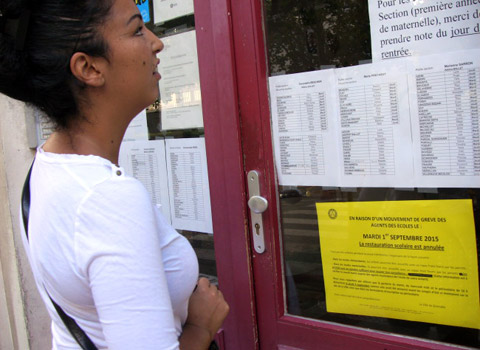 Une mère de famille devant l'école maternelle de la Bajatière à Grenoble, lit les messages prévenant de la grève des agents le jour de la rentrée le 1er septembre 2015. © Séverine Cattiaux - placegrenet.fr