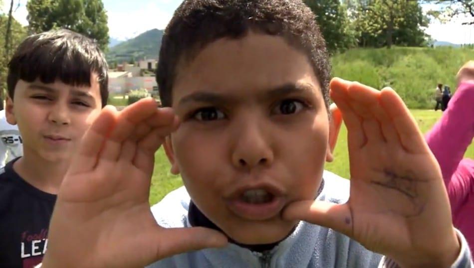 Un enfant habitant le quartier de la Villeneuve imite une caméra avec ses mains. Extrait du documentaire La Villeneuve, l'utopie malgré tout, de V. Massot et F. Viénot.