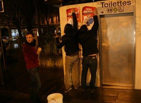 Des lecteurs du journal satirique Fakir collent des affiches du film Merci Patron à Grenoble, en soutien contre la censure. © Florent Mathieu - placegrenet.fr