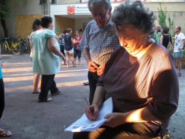 Deux retraités signent la pétition contre le retrait de la Ville de la Maison Des Habitants Bajatiere.© Séverine Cattiaux – Place Gre'net