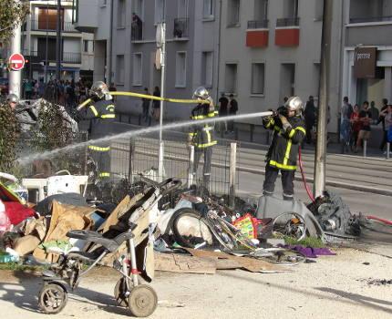 Deux jours après une attaque nocturne dans le camp Valmy à Grenoble, un incendie criminel a embrasé des poubelles et un véhicule, ce lundi 22 mai. Les pompiers essaient d'éteindre l'incendie criminel ayant causé la destruction d'une voiture et de poubelles.