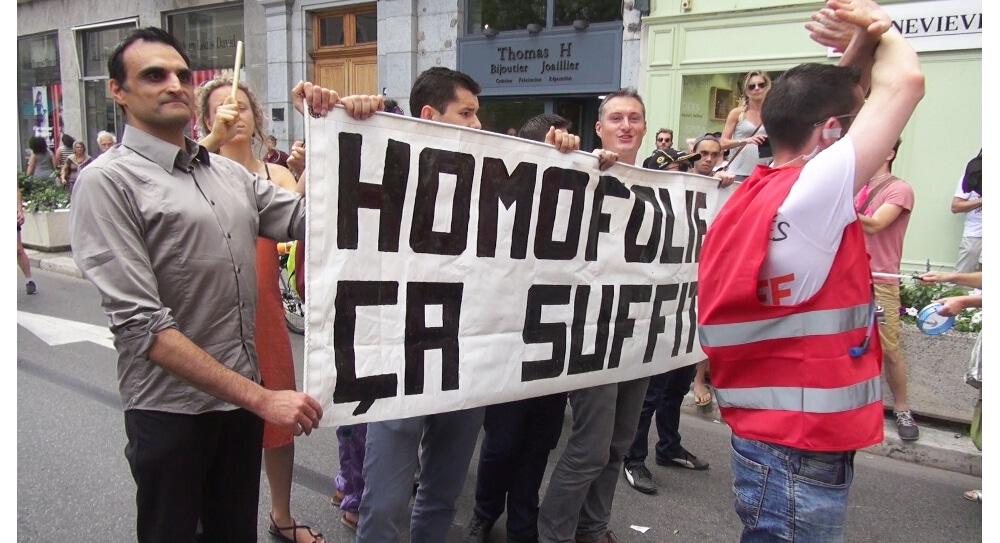 """Franck Sinisi (à gauche) derrière la banderole """"Homofolie ça suffit"""" lors de la Marche des Fiertés 2017 à Grenoble. © Joël Kermabon - Place Gre'net"""