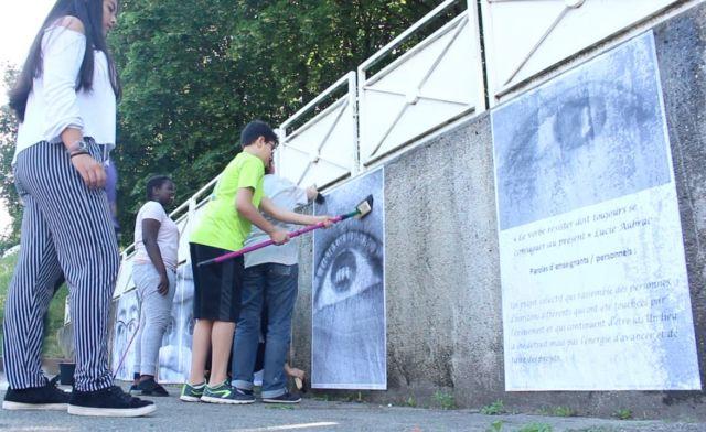Ce jeudi, les élèves du collège Lucie Aubrac ont procédé à des collages d'affiches sur leur ancien collège, leur nouveau, et le chemin qui relie les deux. Sur les affiches, en plus des photos, on peut voir des phrases concernant le projet artistique, rédigées par les participants.