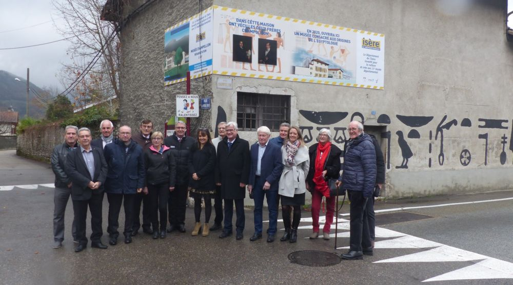 En visite, les élus du Département et l'équipe du musée Champollion prennent la pose. Derrière eux le mur longeant la propriété Champollion orné de hiéroglyphes © Florent Mathieu - Place Gre'net