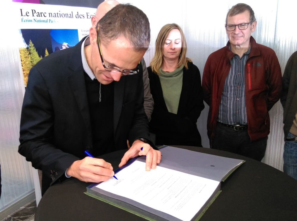 Pierre Commenville signe la convention Valecrin sous le regard de Christelle Méheut et de Pierre Mériaux, conseiller municipal de Grenoble délégué au Tourisme et à la Montagne. © Florent Mathieu - Place Gre'net