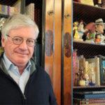 Jacques Glénat devant une vitrine de figurines de bande dessinée.