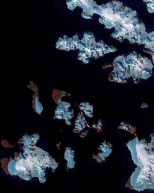 L'image montre les glaciers (de couleurs bleu et blanche) sur les terres (de couleur cuivre) de l'archipel François-Joseph, au nord du 80e parallèle dans l'océan Arctique (en noir). Les glaciers (bleus) sont peu ou pas recouverts de neige (blanche), ce qui indique clairement une perte importante de masse. © Copernicus Sentinel 2017