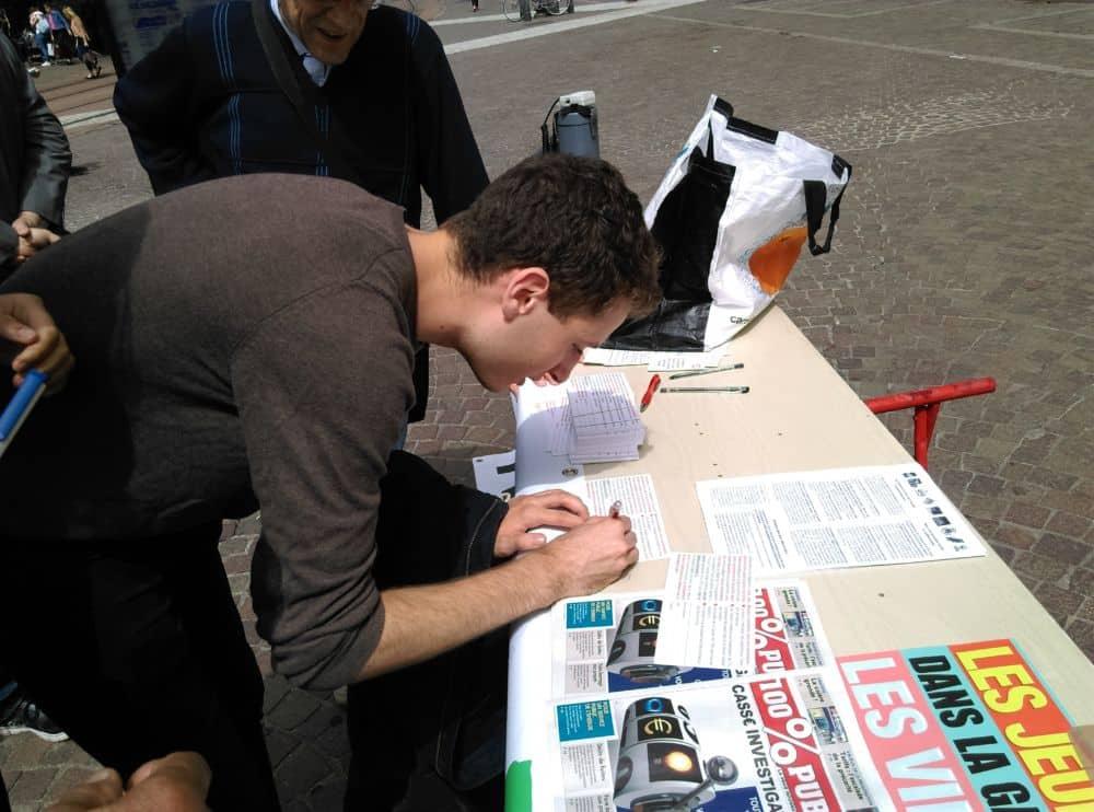 Des jeunes aussi s'arrêtent pour signer. © Florent Mathieu - Place Gre'net