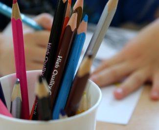 Un enfant dessine sur une feuille avec des crayons de couleur dans un pot devant lui. © Alicja - Pixabay