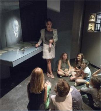 Gratuité des actions de médiation à destination des élèves visitant les musées départementaux de l'Isère. Des élèves écoutent attentivement une médiatrice. © Département de l'Isère