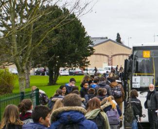 Un groupe d'élèves s'apprête à monter dans un bus scolaire. DR