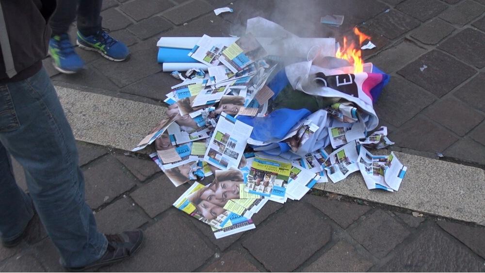 Des opposants à la réforme des retraites brûlent les flyers de la campagne d'Émilie Chalas en marge d'une manifestation. © Joël Kermabon - Place Gre'net