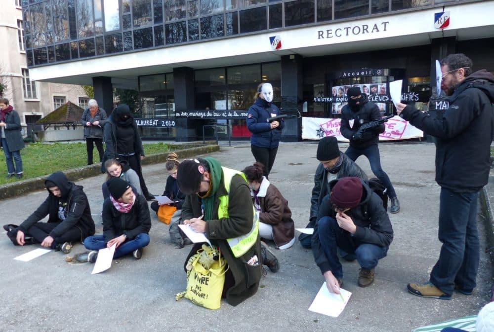 Élèves à genoux et surveillants en uniforme : les E3C mis en scène par les manifestants © Florent Mathieu - Place Gre'net