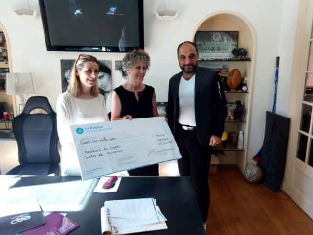 Nathalie Béranger et Catherine Bolze remettent un chèque symbolique de 106 000 euros à Jacques Reboh, président du club des Brûleurs de Loups. © Région Auvergne-Rhône-Alpes