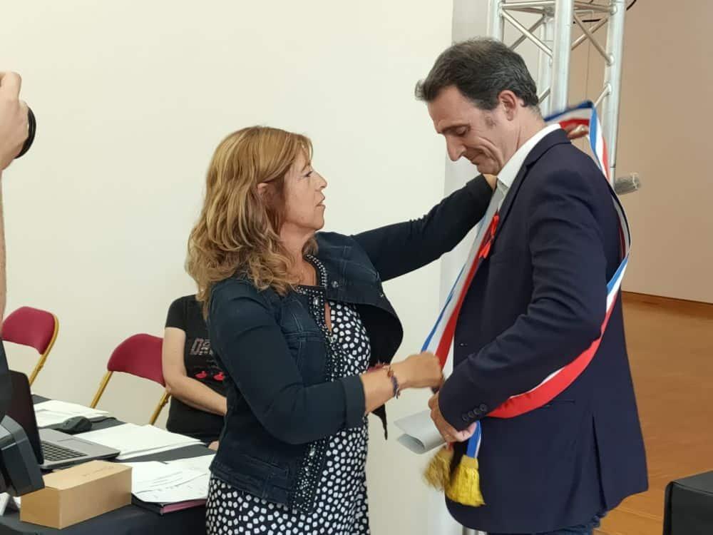 Remise de l'écharpe au maire après l'élection au CM