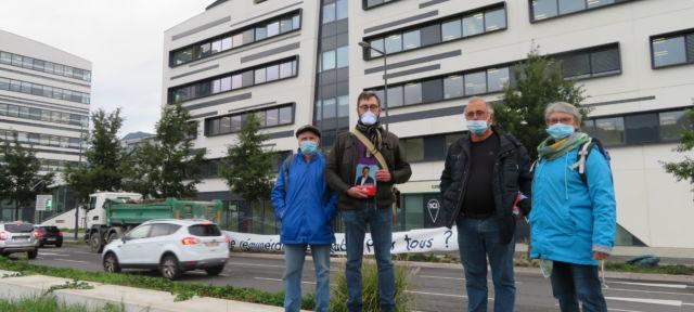 Sur la banderole derrière les militants, on peut lire : « Des profits pour les financiers ou une rémunération équitable pour tous ? » © Tim Buisson - Place Gre'net.