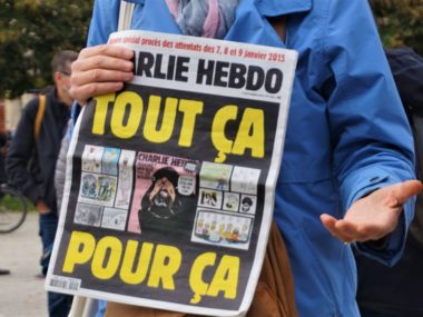 Une manifestante exhibe le numéro de Charlie Hebdo sorti début septembre © Simon Marseille – Place Gre'net