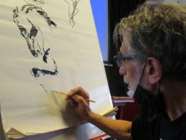 Edmond Baudoin en train de dessiner devant quelques curieux à la bibliothèque du centre-ville de Grenoble. © Tim Buisson – Place Gre'net