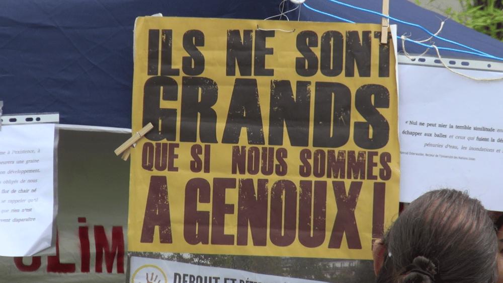 """Pancarte """"Ils ne sont grands que si nous sommes à genoux"""" pendant un rassemblement devant le tribunal de Grenoble le 30 juin 2021(c) Ilan Khalifa--Delclos   Place Gre'net"""