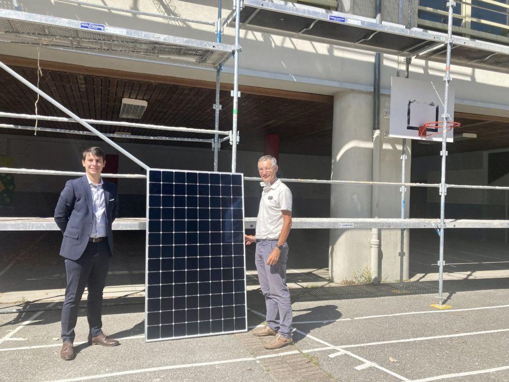 Jean-Baptiste Caillet (à gauche) et Philippe Cardin posent dans la cour de l'école élémentaire du Haut-Meylan avec un panneau photovoltaïque © Ville de Meylan