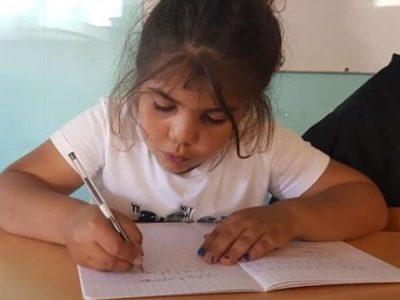 COUV Enfant écrivant sur un cahier. Soutien scolaire de l'association