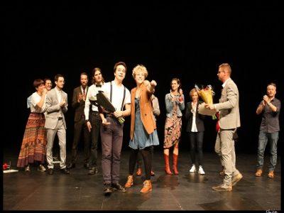 Mathis Druelle, le gagnant d'Eloquentia Grenoble 2019, avec Auxane Menezo, cofondatrice de l'antenne de Grenoble du concours d'éloquence. En arrière plan le jury et les autres candidats du carré final. © Eloquentia